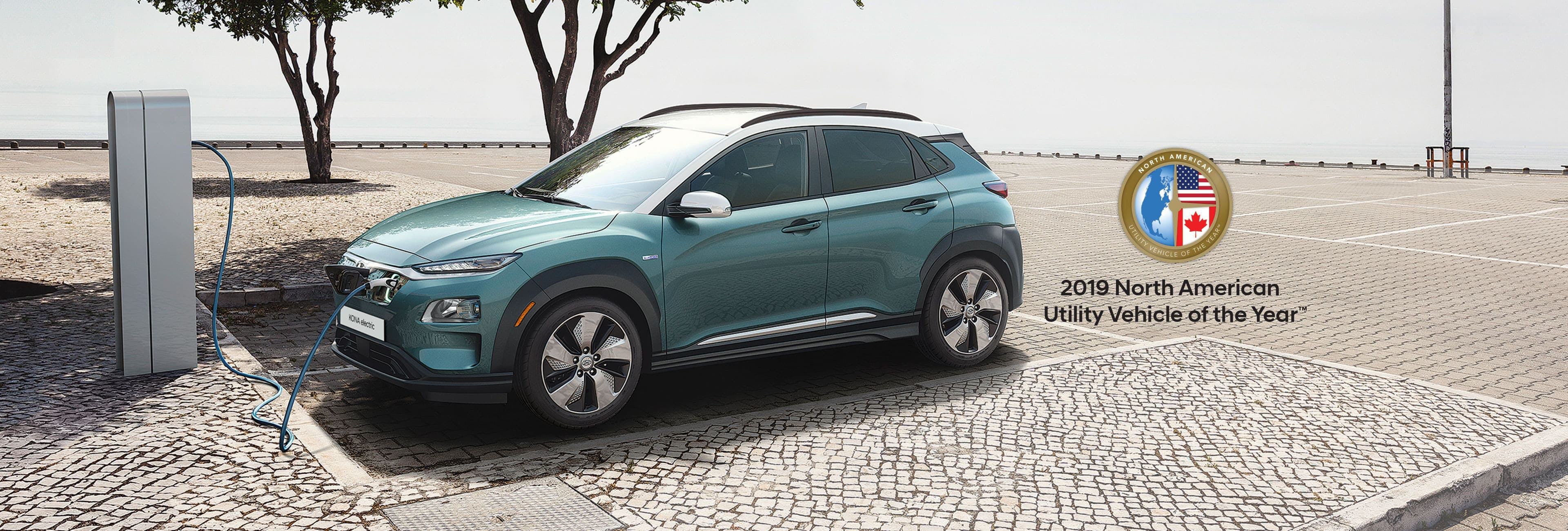 A light teal Kona Electric charges at a charge station