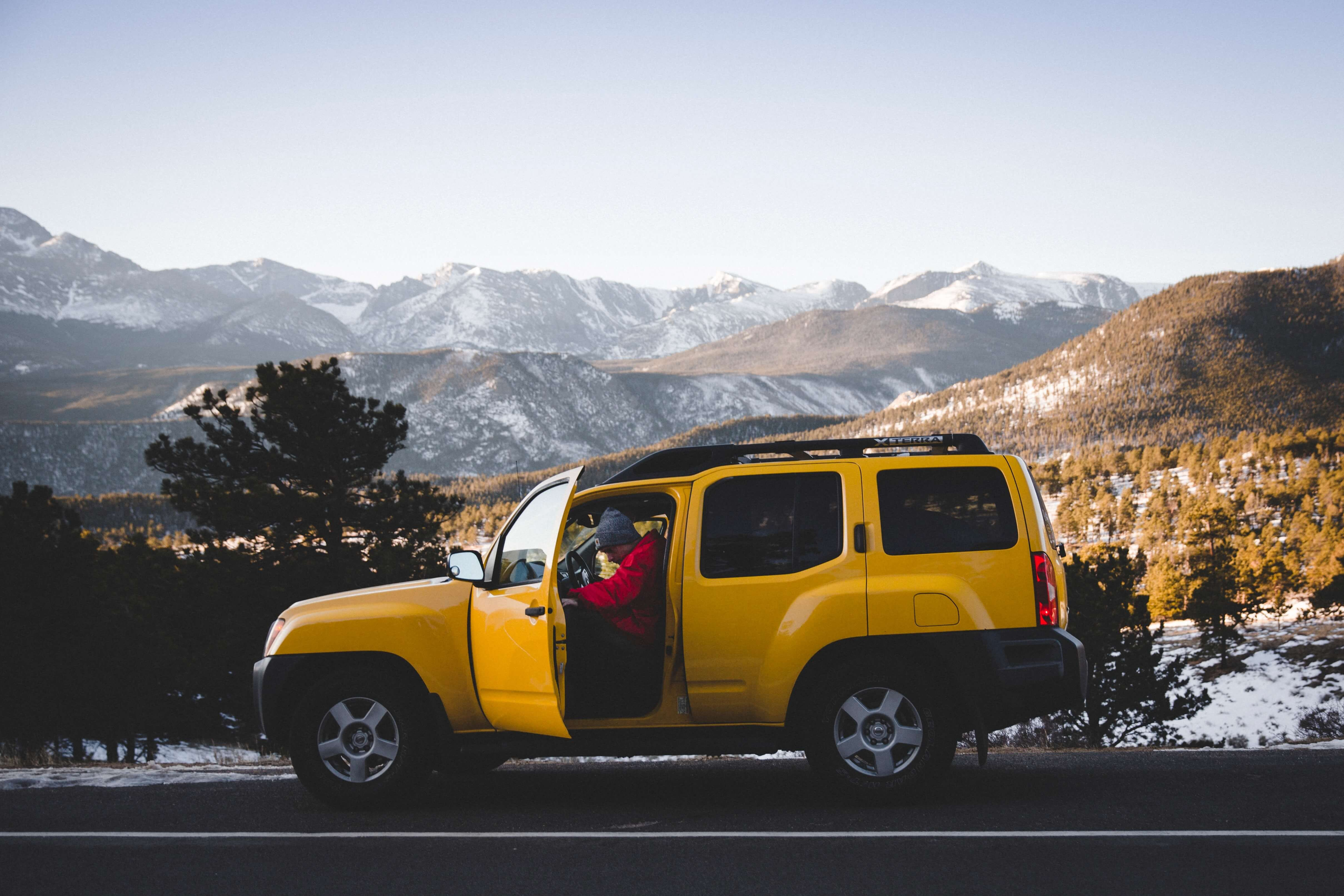 A family in a yellow SUV parked by the mountains