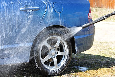 Spray washing a car wheel