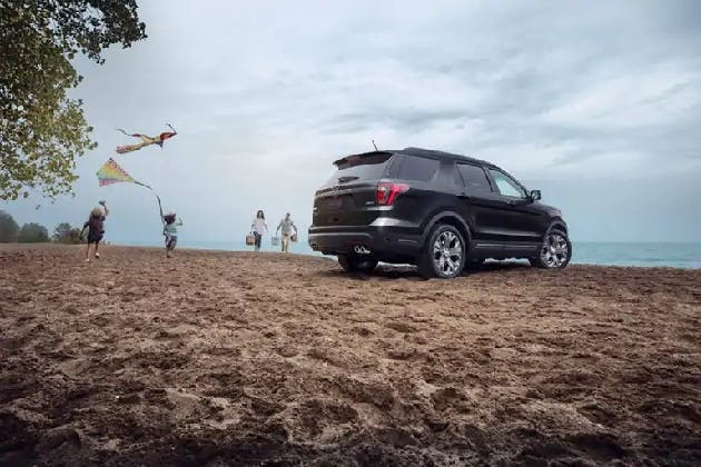 A family plays at a lake in Saskatchewan while their Ford Explorer sits parked near by