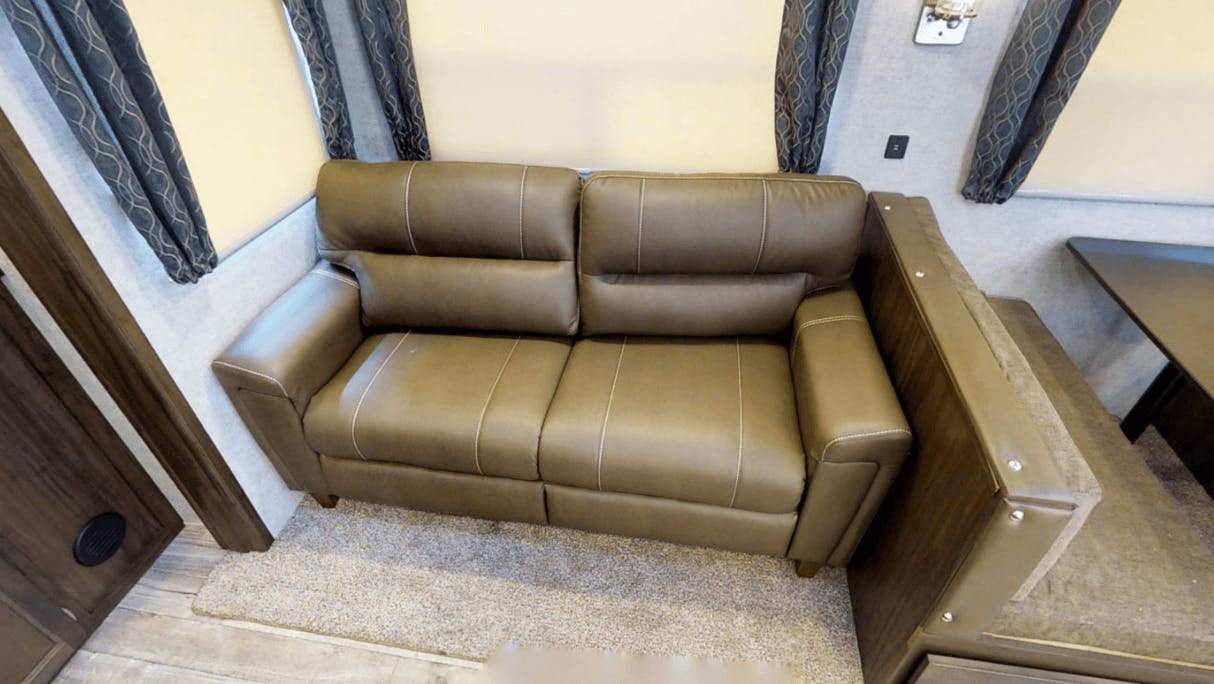 Comfy tan faux leather sofa in Arctic Wolf RV Unit