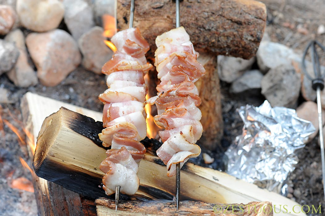 bacon over a campfire rolled up on skewers
