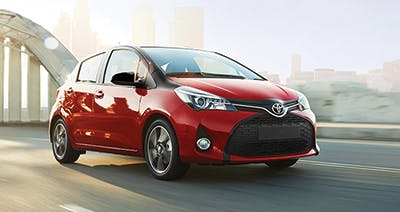 Red 2016 Toyota Yaris on a bridge